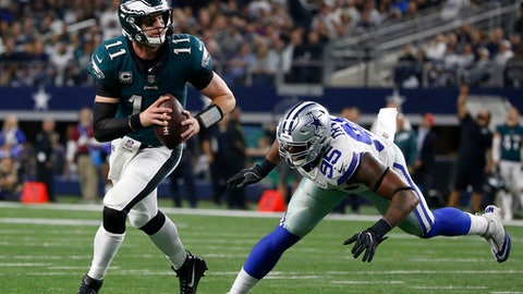 Philadelphia Eagles quarterback Carson Wentz (11) evades pressure from Dallas Cowboys' David Irving (95) before throwing a pass for a two-point conversion to wide receiver Alshon Jeffery in the second half of an NFL football game, Sunday, Nov. 19, 2017, in Arlington, Texas. (AP Photo/Ron Jenkins)