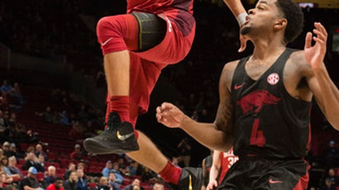 Oklahoma guard Trae Young, left, scores a basket as he is guarded by Arkansas guard Daryl Macon, right, during the first half in an NCAA college basketball game at the Phil Knight Invitational Tournament in Portland, Ore., Thursday, Nov. 23, 2017. (AP Photo/Troy Wayrynen)