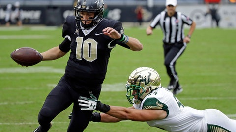 Central Florida quarterback McKenzie Milton (10) runs for a 3-yard touchdown past South Florida linebacker Nico Sawtelle during the first half of an NCAA college football game, Friday, Nov. 24, 2017, in Orlando, Fla. (AP Photo/John Raoux)