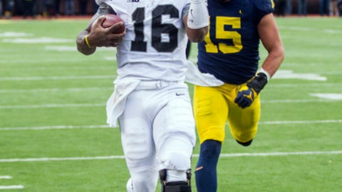 Ohio State quarterback J.T. Barrett (16) scores a touchdown, defended by Michigan defensive lineman Chase Winovich (15), in the second quarter of an NCAA college football game in Ann Arbor, Mich., Saturday, Nov. 25, 2017. (AP Photo/Tony Ding)