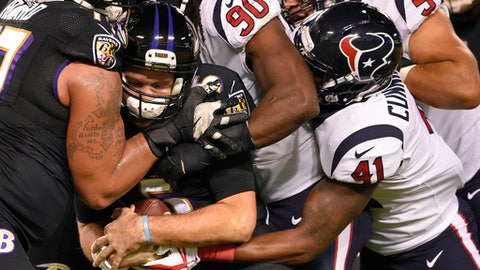 Baltimore Ravens quarterback Joe Flacco, second from left, is sacked by Houston Texans outside linebacker Jadeveon Clowney in the first half of an NFL football game, Monday, Nov. 27, 2017, in Baltimore. (AP Photo/Nick Wass)