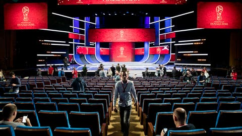 Journalists walk in the concert hall of the State Kremlin Palace where Friday's final draw for the 2018 soccer World Cup will take place in the State Kremlin Palace in Moscow, Russia, Thursday, Nov. 30, 2017. (AP Photo/Pavel Golovkin)