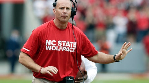 In this Saturday, Nov. 4, 2017 file photo, North Carolina State head coach Dave Doeren reacts during the first half of an NCAA college football game against Clemson in Raleigh, N.C. A person with knowledge of the situation says North Carolina State and Dave Doeren have agreed on a five-year deal after the coach had talked with Tennessee officials about the school's opening. The person spoke to The Associated Press Thursday, Nov. 30, 2017 on condition of anonymity because N.C. State hasn't publicly announced the agreement. (AP Photo/Gerry Broome, File)