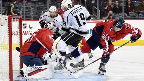 Los Angeles Kings center Alex Iafallo (19) works for the puck against Washington Capitals goalie Braden Holtby (70) and defenseman Madison Bowey (22) during the first period of an NHL hockey game, Thursday, Nov. 30, 2017, in Washington. (AP Photo/Nick Wass)