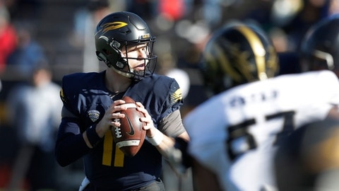 FILE - In this Nov. 24, 2017 file photo, Toledo quarterback Logan Woodside looks downfield during the first half of an NCAA college football game against the Western Michigan, in Toledo, Ohio. Woodside and coach Jason Candle of the University of Toledo received postseason football honors from the Mid-American Conference, the league announced Wednesday, Nov. 29, 2017 . Woodside was named offensive player of the year for the league, while Candle was voted coach of the year in a ballot of the league's coaches and selected media. Woodside also received the Vern Smith Leadership Award, which through the years has morphed into a MAC MVP award.  (AP Photo/Carlos Osorio, File)