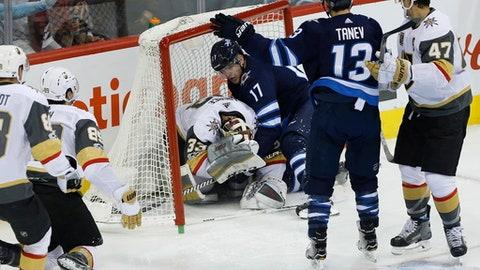 Winnipeg Jets' Adam Lowry (17) crashes into Las Vegas Golden Knights goalie Maxime Lagace (33) during third-period NHL hockey game action in Winnipeg, Manitoba, Friday, Dec. 1, 2017. (John Woods/The Canadian Press via AP)