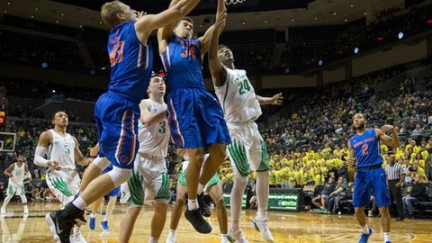 Boise State's Alex Hobbes (34) pulls down an offensive rebound in front of Oregon's Abu Kigab (24) and Payton Pritchard (3) during an NCAA college basketball game in Eugene, Ore., Friday, Dec. 1, 2017. (Brian Davies/The Register-Guard via AP)