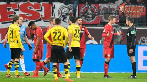 Referee Robert Hartmann, right, shows the red card to Leverkusen's Wendell, left, during the German Bundesliga soccer match between Bayer Leverkusen and Borussia Dortmund in Leverkusen, Germany, Saturday, Dec. 2, 2017. (AP Photo/Martin Meissner)
