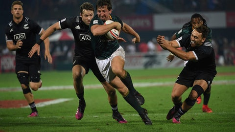 South Africa's Kwagga Smith, front, slips through New Zealand's defence in the final of the World Rugby Sevens Series in Dubai, the United Arab Emirates, Saturday, Dec. 2, 2017. South Africa beat New Zealand 24-12, defending its last year's title. (AP Photo/Martin Dokoupil)