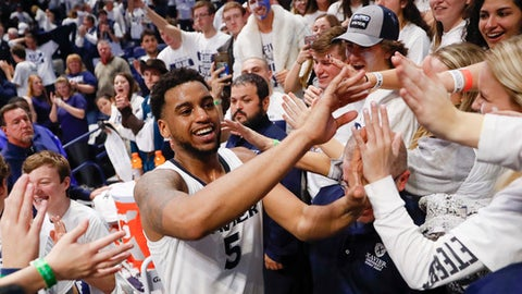 Xavier's Trevon Bluiett (5) celebrates with fans after an NCAA college basketball game against Cincinnati, Saturday, Dec. 2, 2017, in Cincinnati. Xavier won 89-76. (AP Photo/John Minchillo)