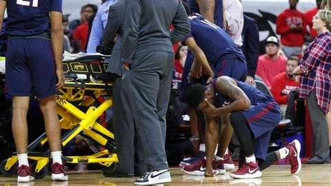 South Carolina State players react as Ty Solomon is attended to after he was injured during the first half of an NCAA college basketball game against North Carolina State at PNC Arena in Raleigh, N.C., Saturday, Dec. 2, 2017.  (Ethan Hyman/The News & Observer via AP)