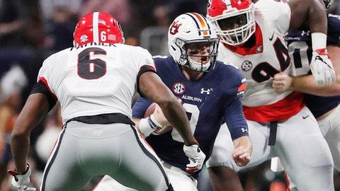 Auburn quarterback Jarrett Stidham (8) runs as Georgia linebacker Natrez Patrick (6) during the first half of the Southeastern Conference championship NCAA college football game, Saturday, Dec. 2, 2017, in Atlanta. (AP Photo/David Goldman)