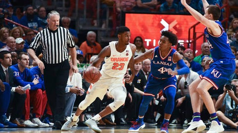 Syracuse's Frank Howard (23) drives to the basket as Kansas Devonte Graham (4) attempts to block his path during the first half of an NCAA college basketball at the HoopHall Miami Invitational tournament Saturday, Dec. 2, 2017, in Miami. Kansas won 76-60. (AP Photo/Gaston De Cardenas)