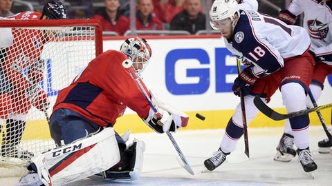 Washington Capitals goalie Braden Holtby (70) stops the puck from Columbus Blue Jackets center Pierre-Luc Dubois (18) during the second period of an NHL hockey game, Saturday, Dec. 2, 2017, in Washington. (AP Photo/Nick Wass)