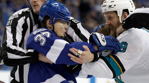 NHL linesman Ryan Daisy, left, tries to break up a fight between Tampa Bay Lightning center Yanni Gourde (37) and San Jose Sharks center Joe Thornton (19) during the second period of an NHL hockey game Saturday, Dec. 2, 2017, in Tampa, Fla. (AP Photo/Chris O'Meara)