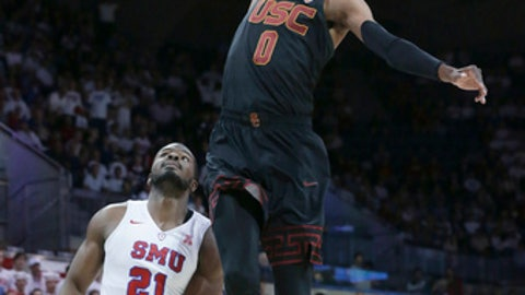 SMU guard Jahmal McMurray (0) goes in for a dunk over SMU guard Ben Emelogu II (21) during the first half of an NCAA college basketball game in Dallas, Saturday, Dec. 2, 2017. (AP Photo/LM Otero)