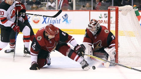 Arizona Coyotes goalie Scott Wedgewood (31) makes a save on a shot as defenseman Luke Schenn (2) tries to clear the puck from the front of the net while New Jersey Devils' Jimmy Hayes (10) skates in during the third period of an NHL hockey game, Saturday, Dec. 2, 2017, in Glendale, Ariz. The Coyotes defeated the Devils 5-0. (AP Photo/Ralph Freso)