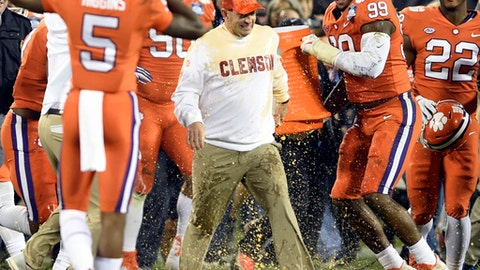 Clemson head coach Dabo Swinney, center, is dunked by players as they celebrate after their win over Miami in the Atlantic Coast Conference championship NCAA college football game in Charlotte, N.C., Saturday, Dec. 2, 2017. (AP Photo/Mike McCarn)