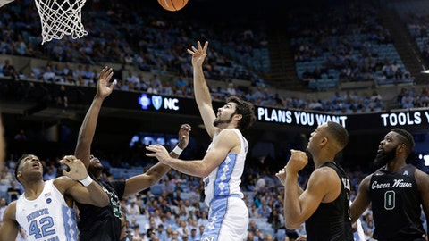 North Carolina's Luke Maye shoots while Tulane's Blake Paul, left, Cameron Reynolds, and Jordan Cornish (0) look on during the first half of an NCAA college basketball game in Chapel Hill, N.C., Sunday, Dec. 3, 2017. North Caroina's Brandon Huffman (42) looks for a rebound. (AP Photo/Gerry Broome)