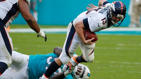 Denver Broncos quarterback Trevor Siemian (13) is sacked by Miami Dolphins defensive tackle Jordan Phillips (97), during the second half of an NFL football game, Sunday, Dec. 3, 2017, in Miami Gardens, Fla. To the left is Denver Broncos offensive guard Max Garcia (76). (AP Photo/Wilfredo Lee)