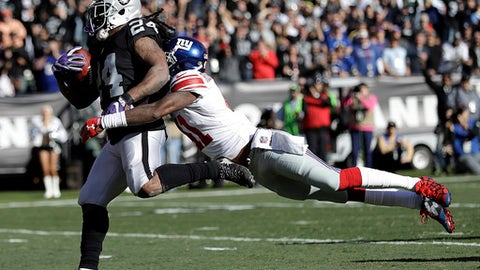 Oakland Raiders running back Marshawn Lynch (24) scores a touchdown in front of New York Giants cornerback Dominique Rodgers-Cromartie during the first half of an NFL football game in Oakland, Calif., Sunday, Dec. 3, 2017. (AP Photo/Marcio Jose Sanchez)