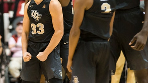 Central Florida's Djordjije Mumin (33), Tacko Fall (24), Terrell Allen (2) and others celebrate the end of an NCAA college basketball game against Alabama, Sunday, Dec. 3, 2017, in Tuscaloosa, Ala. (AP Photo/Laura Chramer)