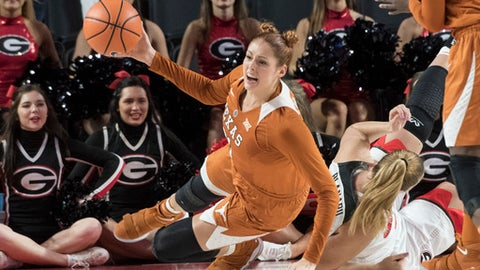 Texas forward Audrey-Ann Caron-Goudreau tries to get a pass off as she hits the floor with while Georgia center Bianca Blanaru, right, defends during the first half of an NCAA college basketball game, Sunday, Dec. 3, 2017, in Athens, Ga. (AP Photo/John Amis)