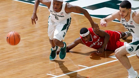 Michigan State's Cassius Winston, left, and Gavin Schilling, right, and Nebraska's Glynn Watson Jr., center, chase the ball during the first half of an NCAA college basketball game Sunday, Dec. 3, 2017, in East Lansing, Mich. (AP Photo/Al Goldis)