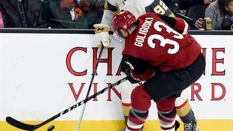 Vegas Golden Knights center Tomas Nosek (92) and Arizona Coyotes defenseman Alex Goligoski battle for the puck during the second period of an NHL hockey game, Sunday, Dec. 3, 2017, in Las Vegas. (AP Photo/David Becker)