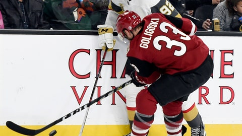 Vegas Golden Knights center Tomas Nosek (92) and Arizona Coyotes defenseman Alex Goligoski battle for the puck during the second period of an NHL hockey game, Sunday, Dec. 3, 2017, in Las Vegas. (AP Photo/David Becker)