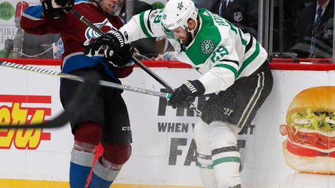 Dallas Stars defenseman Greg Pateryn, right, pushes Colorado Avalanche defenseman Anton Lindholm, of Sweden, into the boards to take possession of the puck during the third period of an NHL hockey game Sunday, Dec. 3, 2017, in Denver. The Stars won 7-2. (AP Photo/David Zalubowski)