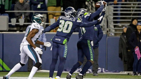 Seattle Seahawks' Byron Maxwell, right, intercepts a pass in the end zone meant for Philadelphia Eagles' Nelson Agholor, left, as Bradley McDougald (30) helps defend during the second half of an NFL football game, Sunday, Dec. 3, 2017, in Seattle. (AP Photo/Ted S. Warren)