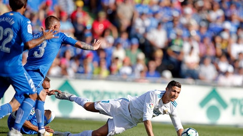 FILE - In this Oct. 14, 2017 file photo, Real Madrid's Cristiano Ronaldo falls during a Spanish La Liga soccer match between Getafe and Real Madrid at the Coliseum Alfonso Perez in Getafe, Spain. Spanish league teams are seldom happy when playing at Getafe's small stadium in southern Madrid, no matter the result of their matches. Win or lose, teams have been complaining of poor field conditions at the Coliseum Alfonso Perez, which has been attracting more attention than the hosts' decent Spanish league campaign so far. (AP Photo/Paul White, File)