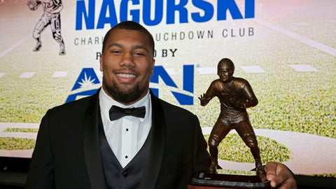 North Carolina State's Bradley Chubb poses with the Bronko Nagusrki trophy for the top defensive player in NCAA college football during a photo opportunity in Charlotte, N.C., Monday, Dec. 4, 2017. (AP Photo/Chuck Burton)