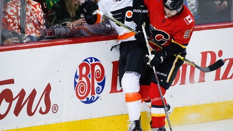 Philadelphia Flyers' Brandon Manning, left, is checked by Calgary Flames' Sam Bennett during the first period of an NHL hockey game, Monday, Dec. 4, 2017 in Calgary, Alberta.  (Jeff McIntosh/The Canadian Press via AP)