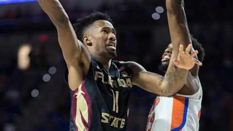 Florida State guard Braian Angola (11) shoots over Florida forward Kevarrius Hayes (13) during the first half of an NCAA college basketball game in Gainesville, Fla., Monday, Dec. 4, 2017. (AP Photo/Ron Irby)