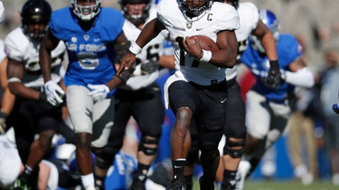 FILE - In this Saturday, Nov. 4, 2017, file photo, Army quarterback Ahmad Bradshaw breaks from the line of scrimmage against Air Force while running an option play in the first half of an NCAA college football game at Air Force Academy, Colo. The triple option has been part of the DNA for Air Force, Navy and Army for decades because it levels the playing field. It's hard to defend and doesn't require big offensive linemen. At its core, the system is centered on a quarterback with plenty of moxie and a fullback with a nose for getting through a tiny crease.  (AP Photo/David Zalubowski, File)
