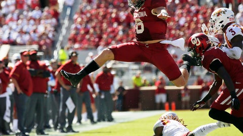 FILE - In this Oct. 7, 2017, file photo, Oklahoma quarterback Baker Mayfield (6) leaps over Iowa State defensive back De'Monte Ruth, bottom, in the second quarter of an NCAA college football game in Norman, Okla. This season Mayfield has passed for 4,340 yards with 41 touchdown passes and just five interceptions, and he has rushed for 310 yards and five more scores. He will be the first quarterback to finish in the top four of the Heisman Trophy balloting three times, and he's favored to claim the award on Saturday. (AP Photo/Sue Ogrocki, File)