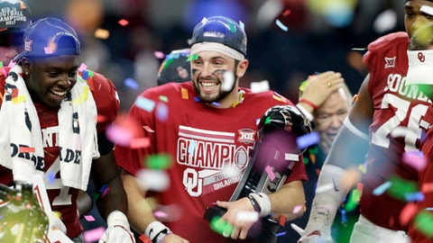 FILE - In this Dec. 2, 2017, file photo, Oklahoma quarterback Baker Mayfield, center, holds his Most Outstanding Player trophy as he celebrates with the team after their 41-17 win in the the Big 12 Conference championship NCAA college football game against TCU, in Arlington, Texas. This season, Mayfield has passed for 4,340 yards with 41 touchdown passes and just five interceptions, and he has rushed for 310 yards and five more scores. He will be the first quarterback to finish in the top four of the Heisman Trophy balloting three times, and he's favored to claim the award on Saturday. (AP Photo/Tony Gutierrez)