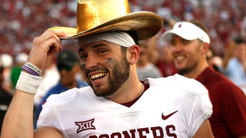 FILE - In this Oct. 14, 2017, file photo, Oklahoma quarterback Baker Mayfield (6) celebrates with the Golden Hat Trophy following the team's 29-24 win over Texas in an NCAA college football game in Dallas. Mayfield will be the first quarterback to finish in the top four of the Heisman Trophy balloting three times, and he's favored to claim the award on Saturday. (AP Photo/Ron Jenkins, File)