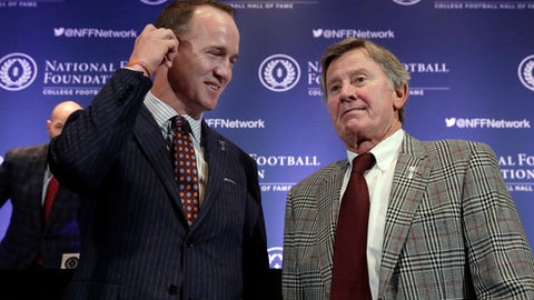 CORRECTS SPELLING TO PEYTON, NOT PAYTON - Former University of Tennessee football quarterback Peyton Manning, left, and former University of Florida football quarterback Steve Spurrier get together after a news conference of the National Football Foundation and College Football Hall of Fame, in New York, Tuesday, Dec. 5, 2017. (AP Photo/Richard Drew)