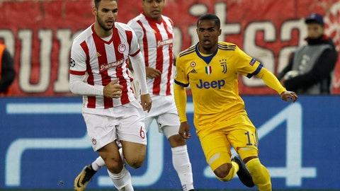 Juventus' Douglas Costa, right, and Olympiakos' Panagiotis Tachtsidis run for the ball during the Champions League group D soccer match between Olympiakos and Juventus at Georgios Karaiskakis stadium at Piraeus port, near Athens, Tuesday, Dec. 5, 2017. (AP Photo/Thanassis Stavrakis)