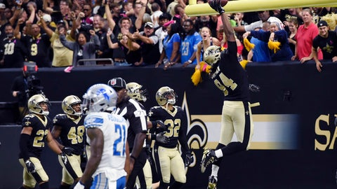 """FILE - In this Oct. 15, 2017, file photo, New Orleans Saints defensive end Cameron Jordan (94) celebrates after returning an interception for touchdown by dunking the football over the goal post in the second half of an NFL football game against the Detroit Lions in New Orleans. Jordan's love of basketball was arguably counterproductive when he was flagged and fined for celebrating by dunking the ball over the goal post. But when Jordan talks about pursuing a """"triple-double"""" in season sacks, tackles for loss and passes defended, coach Sean Payton is all about it. (AP Photo/Bill Feig, File)"""