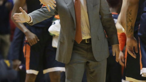 Virginia coach Tony Bennett congratulates his players during the first half of an NCAA college basketball game against West Virginia, Tuesday Dec. 5, 2017, in Morgantown, W.Va. (AP Photo/Raymond Thompson)