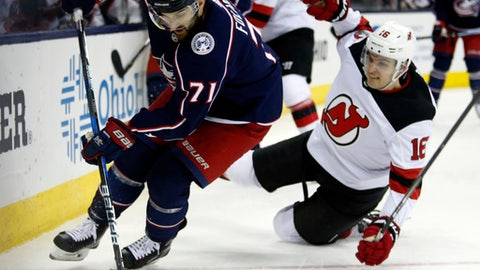 Columbus Blue Jackets forward Nick Foligno, left, controls the puck in front of New Jersey Devils defenseman Steven Santini during the second period of an NHL hockey game in Columbus, Ohio, Tuesday, Dec. 5, 2017. (AP Photo/Paul Vernon)