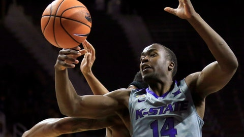 Kansas State forward Makol Mawien (14) rebounds against South Carolina Upstate forward Ramel Thompkins, back, during the second half of an NCAA college basketball game in Manhattan, Kan., Tuesday, Dec. 5, 2017. (AP Photo/Orlin Wagner)