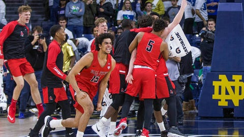 Ball State players celebrate following an NCAA college basketball game against Notre Dame on Tuesday, Dec. 5, 2017, in South Bend, Ind. Ball State won, 80-77. (AP Photo/Robert Franklin)