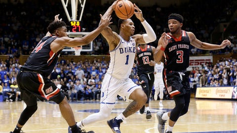 Duke's Trevon Duval (1) drives between Saint Francis (Pa.)'s Andre Wolford and Jamaal King (3) during the first half of an NCAA college basketball game in Durham, N.C., Tuesday, Dec. 5, 2017. (AP Photo/Gerry Broome)