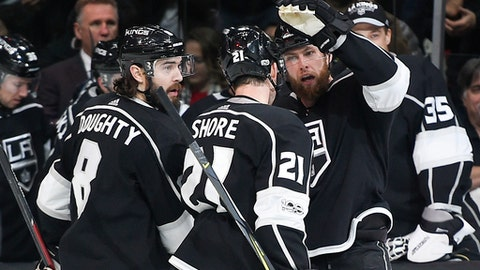 Los Angeles Kings defenseman Jake Muzzin, right, celebrates with center Nick Shore, center, and defenseman Drew Doughty after scoring a goal during the second period of an NHL hockey game against the Minnesota Wild in Los Angeles, Tuesday, Dec. 5, 2017. (AP Photo/Kelvin Kuo)