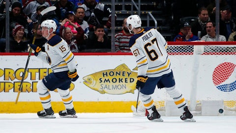 Buffalo Sabres center Jack Eichel, left, raises his stick after scoring an empty-net tally as left wing Benoit Pouliot skates in to congratulate Eichel during the third period of an NHL hockey game against the Colorado Avalanche Tuesday, Dec. 5, 2017, in Denver. Buffalo won 4-2. (AP Photo/David Zalubowski)